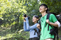 Chinese friends with digital camera on hike in forest — Stock Photo
