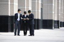 Des hommes d'affaires chinois regardent des documents devant un gratte-ciel — Photo de stock