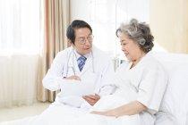 Chinesischen Arzt zeigt Krankenakte Patienten im Krankenhaus — Stockfoto