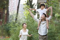Chinese father carrying son on shoulders with mother in city garden — Stock Photo