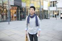 Китаец в шарфе стоит с сумкой на улице — стоковое фото