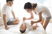 Chinese mother holding hands with baby boy on bed — Stock Photo