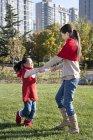 Китайский мать и дочь, взявшись за руки и спиннинг в парке — стоковое фото