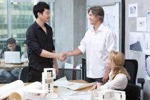 Masculinos arquitetos apertando as mãos no escritório — Fotografia de Stock