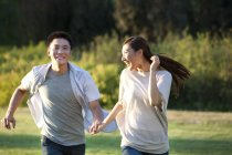 Chinese couple holding hands, laughing and running in park — Stock Photo