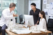 Mature man and chinese architects working in office — Stock Photo