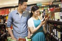 Chinesisches Ehepaar Wein im Supermarkt kaufen — Stockfoto