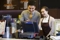 Cafetería china tendero y camarera usando caja registradora — Stock Photo