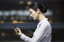 Vista laterale della donna di affari cinese utilizzando smartphone nell'edificio per uffici — Foto stock