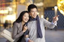 Chinese man pointing at store window while strolling with woman — Stock Photo