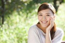 Portrait d'une femme chinoise dans le parc avec la main sur le menton — Photo de stock