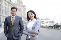 Китайские бизнесмены, стоящие с оружием на перекрестке в финансовом районе — стоковое фото