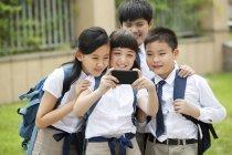 Chinese schoolchildren using smartphone in school yard — Stock Photo