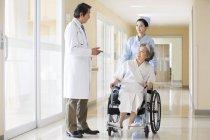 Chinesische medizinische Arbeiter kümmert sich um ältere Frau im Rollstuhl — Stockfoto