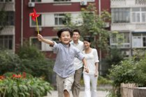 Chinese boy running with pinwheel with parents in background — Stock Photo