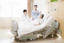 Trabajadores médicos chinos con el paciente en el hospital - foto de stock