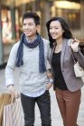 Fashionable Chinese couple on street with shopping bags — Stock Photo