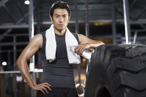 Chinese man resting at gym with towel and water — Stock Photo