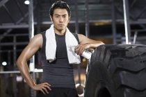 Homem chinês descansando no ginásio com água e toalha — Fotografia de Stock