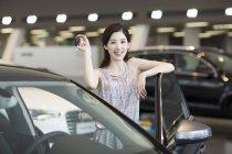 Mujer China con llaves para auto nuevo en showroom - foto de stock