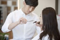 Chinese barber cutting female customer hair — Stock Photo