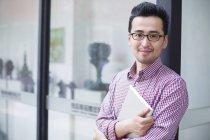 Homem chinês segurando tablet digital e olhando na câmera — Fotografia de Stock