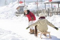 Chinese children playing with sled in snow — Stock Photo
