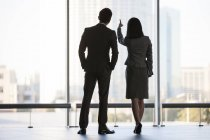 Business people looking through window in office building, rear view — Stock Photo