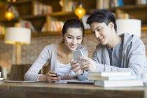 Étudiants chinois à l'aide de smartphone dans café — Photo de stock