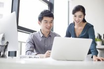 Chinese business co-workers using laptop — Stock Photo