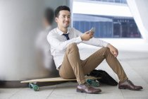 Chinese businessman sitting on skateboard with smartphone — Stock Photo