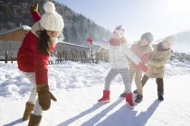 Chinese elementary age children playing in snow at village — Stock Photo