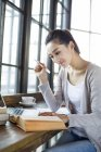 Étudiante chinoise étudiant dans un café avec livre — Photo de stock