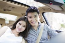 Chinese couple posing together in car — Stock Photo