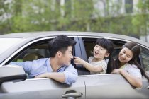 Chinese family riding and leaning out of car — Stock Photo