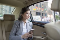 Chinese businesswoman holding smartphone in car — Stock Photo