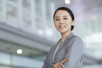 Portrait of Chinese businesswoman standing with arms crossed — Stock Photo