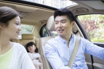 Chinese family riding in car and smiling — Stock Photo