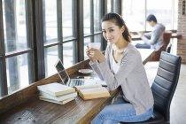 Étudiante chinoise assise dans un café avec café — Photo de stock