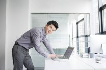 Homme d'affaires chinois utilisant un ordinateur portable dans le bureau — Photo de stock
