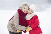 Бабушка и внучка Китая обнимаются на снегу — стоковое фото