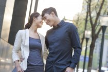 Chinese couple touching foreheads on street — Stock Photo