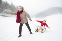 Abuela China tirando a nieta en trineo - foto de stock
