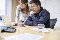 Pessoas de negócios chineses usando laptop na sala de bordo — Fotografia de Stock