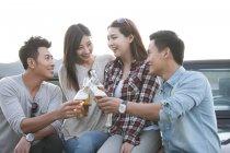 Китайський друзів, сидячи на автомобіль з пивом — стокове фото