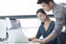 Collègues d'affaires chinois utilisant l'ordinateur portable au bureau — Photo de stock