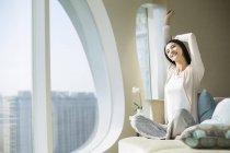 Femme chinoise étirant sur le canapé le matin à l'intérieur de la maison — Photo de stock