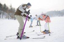 Genitori cinesi, insegnare ai bambini sciare nella stazione sciistica — Foto stock
