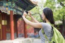 Donna cinese che scatta foto con smartphone al Tempio di Lama — Foto stock