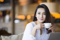 Chinesin trinkt Kaffee im Café — Stockfoto